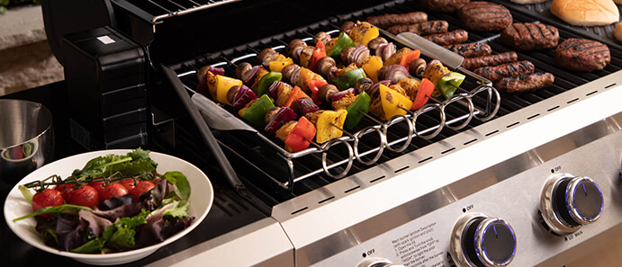Fire Mountain Stainless Steel Kebab Rack with skewered meat and veg alongside other chargrilled food on the Premier Plus 6 Burner BBQ with LED knobs