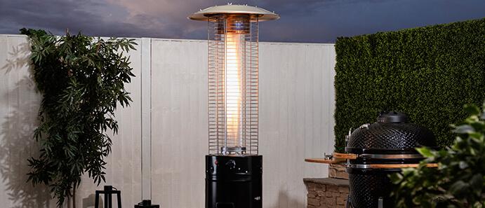 Fire Mountain 14 kW Gas Patio Heater in backyard setting with glowing flame